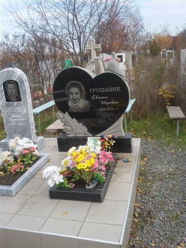 Памятник в виде сердца с резными голубями