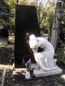 Памятник из черного гранита со скульптурой скорбящей матери