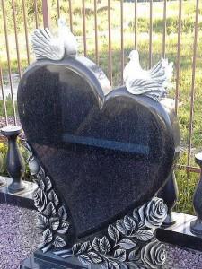 Резной памятник в виде сердца с двумя голубями