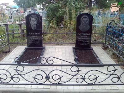 Памятники из черного гранита с металлической оградой