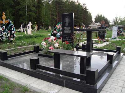 Памятник с черного гранитной оградой, лавочкой и столом