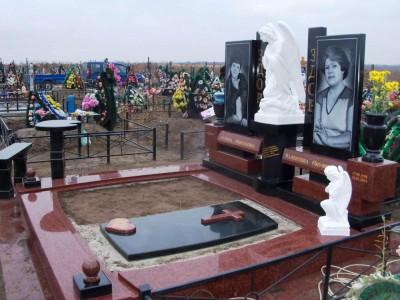 Черно-красный гранитный памятник со скульптурой ангелочка