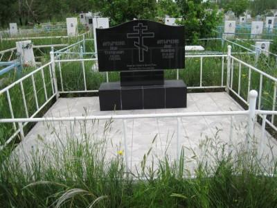 Черный двойной памятник с металлической оградой