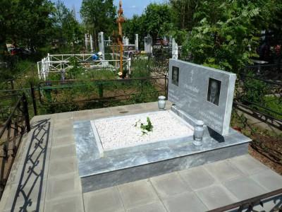 Недорогой двойной памятник серого цвета с металлической оградой