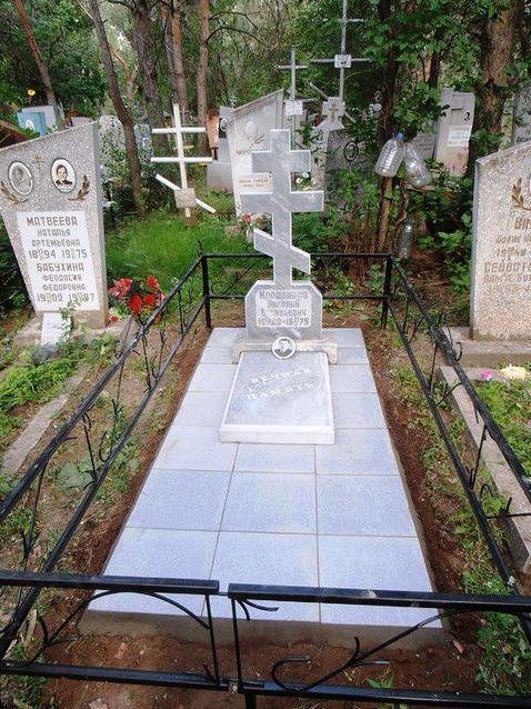 Надгробный памятник в виде креста серого цвета