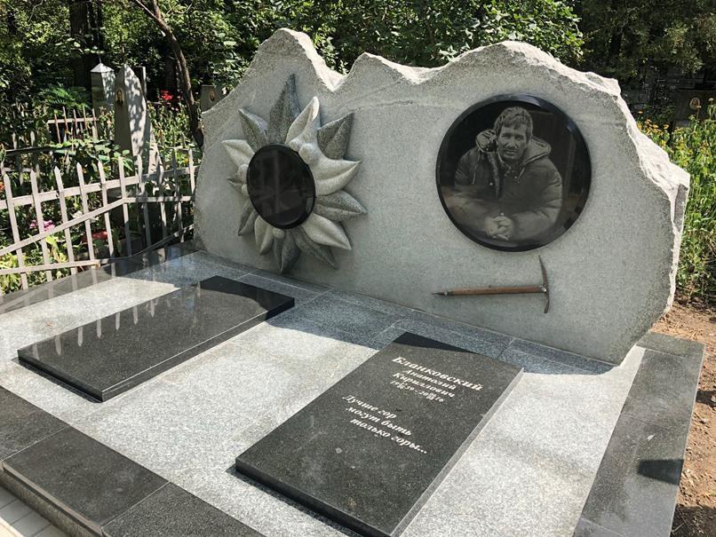 Памятник из серого гранита альпинисту человеку любящему горы с цветком эдельвейса