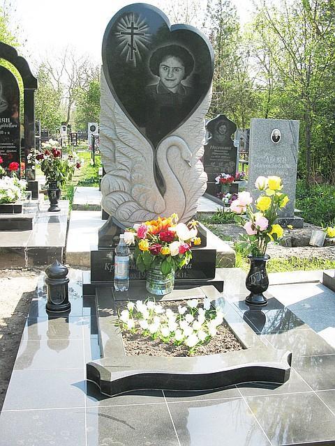 Гранитный памятник с резным лебедем на могилу женщины