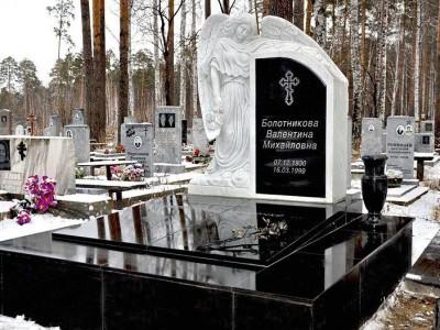Памятник с резным ангелом и высоким цветником
