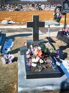 Могильный памятник с крестом черного цвета