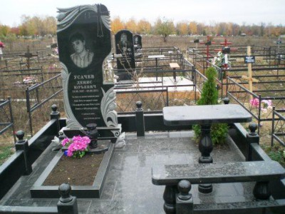 Памятник с гранитной оградой и столом для юноши