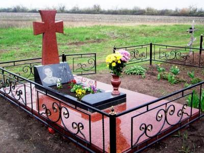Красный гранитный памятник в виде креста