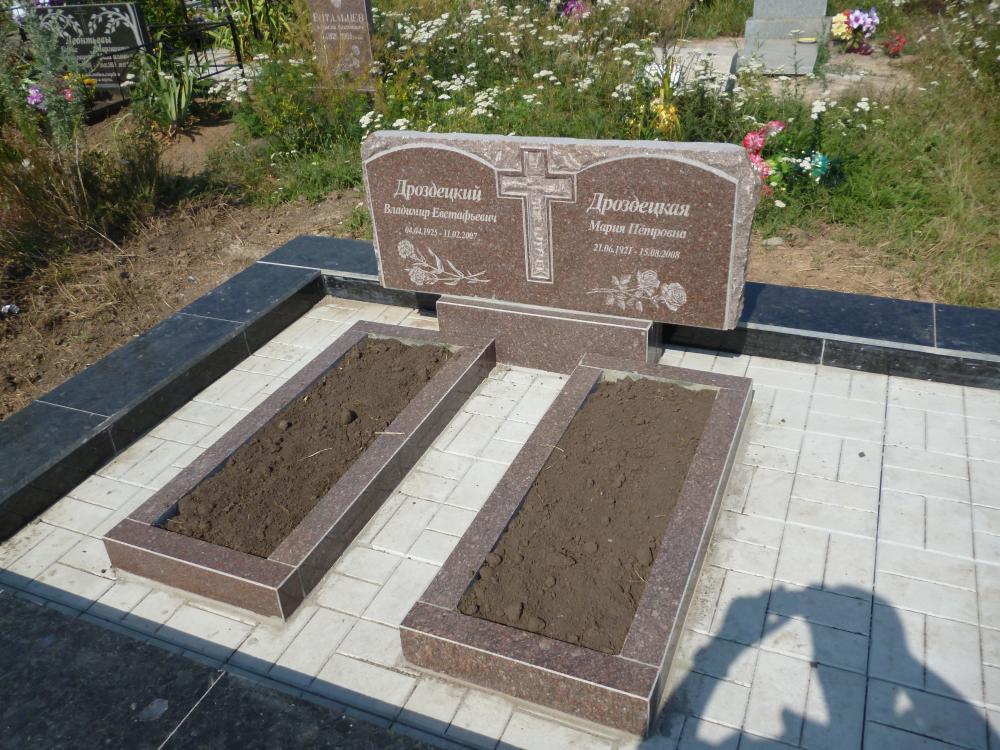 Памятник с резным крестом и с открытыми гранитными цветниками